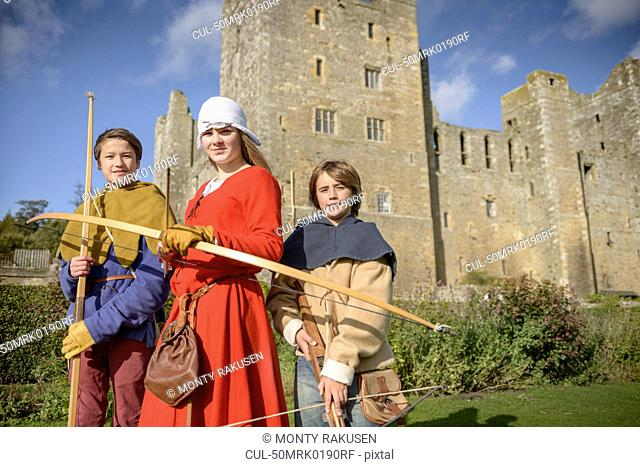 Students in period dress holding weapons