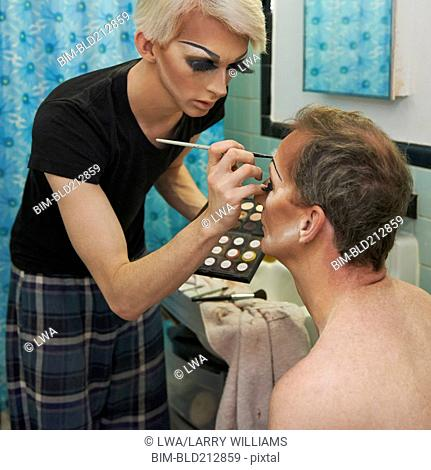 Drag queen applying colleague's makeup in bathroom