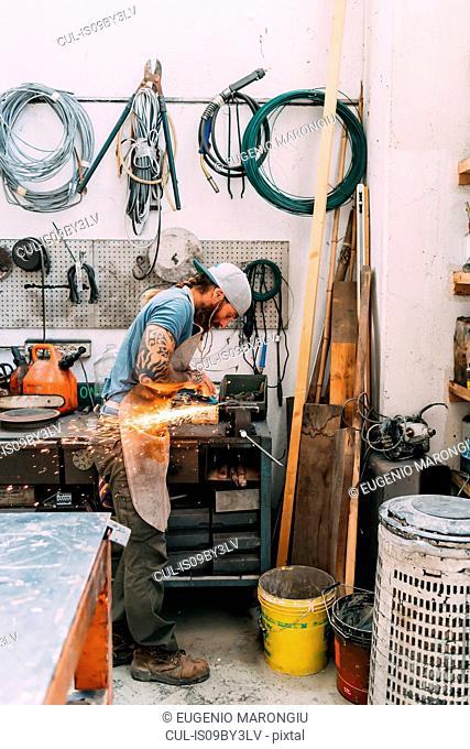 Axe maker using steel grinder in workshop