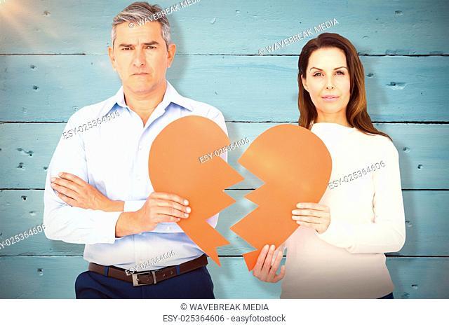 Composite image of portrait of couple holding broken heart shape paper