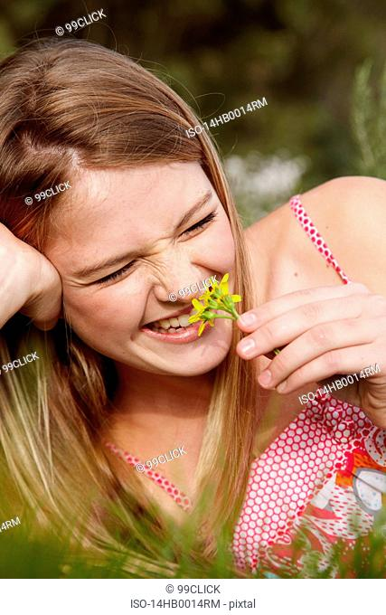 Woman laughing smelling flower in field