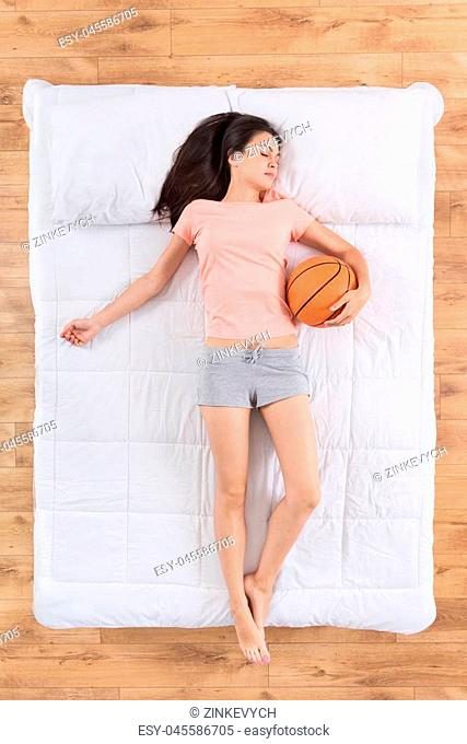 Real fan. Flat lay of delighted young woman holding basketball while sleeping on her back on white bed and dreaming of big sport
