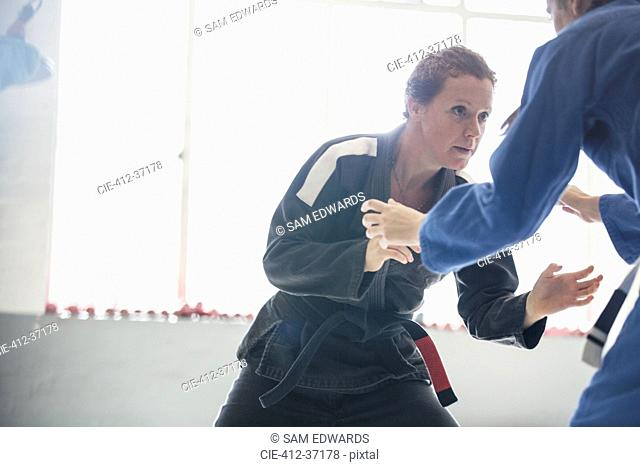 Determined, tough woman practicing judo in gym