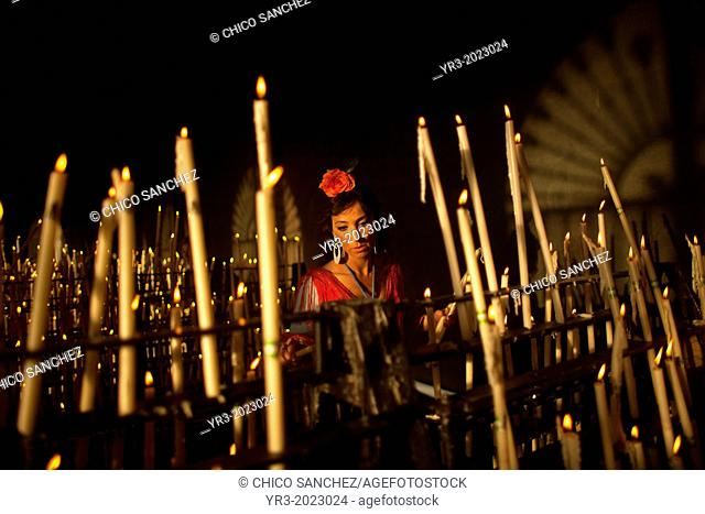 A woman lights a candle in the Votive Room of the shrine of the Virgin of Rocio, in Almonte, Donana National Park, Huelva province, Andalusia, Spain, May 17