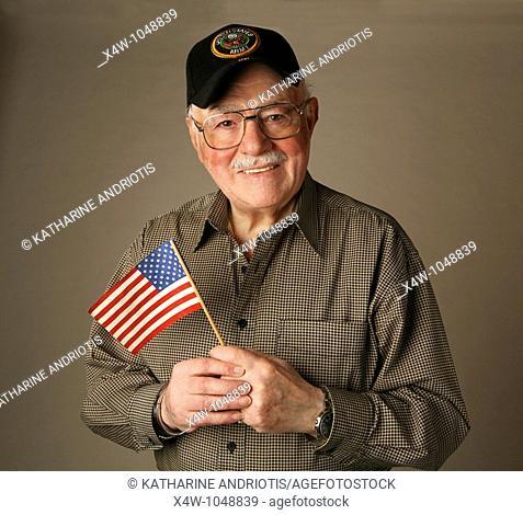 An proud American senior World War II veteran holding flag