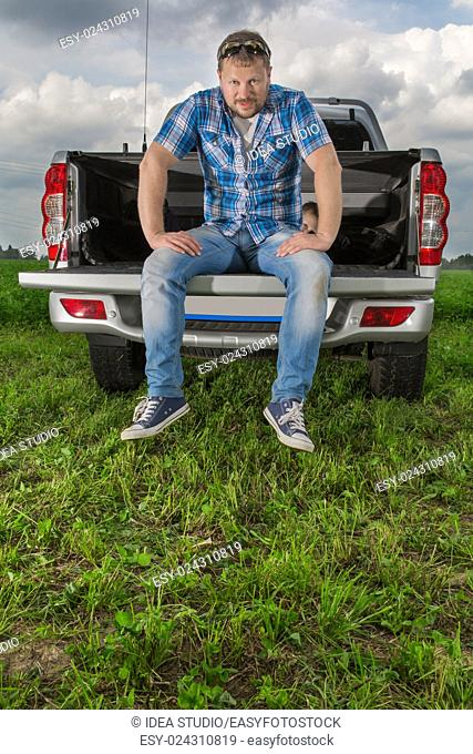 Solid man sitting on car trunk on natural background