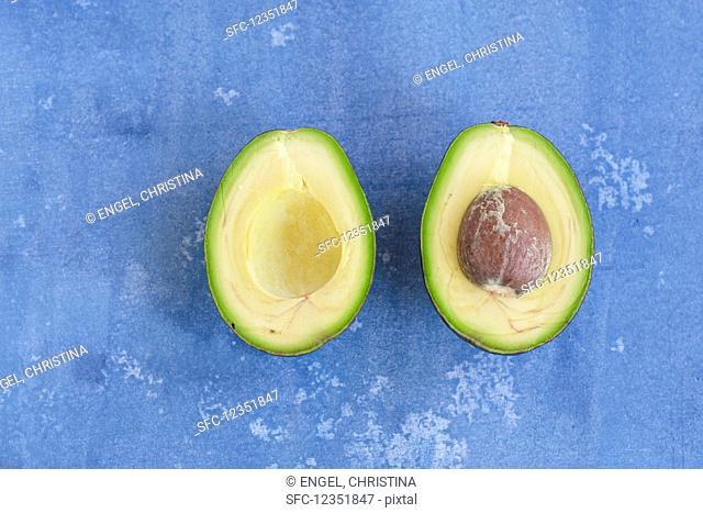 A halved avocado on a blue background