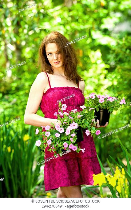 A pretty 25 year old brunette woman holding 2 potted pink petunias in a garden smiling at the camera