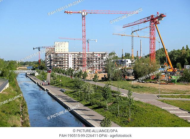 13 May 2019, Saxony, Leipzig: Construction cranes rotate over the newly emerging residential area at the Lindenauer Hafen harbour in Leipzig