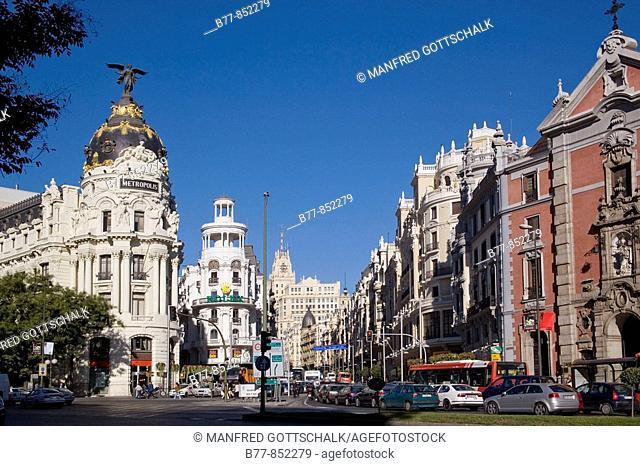Spain, Madrid, Centro, busy intersection of Gran Via and Calle Alcalár with Edificios Metropolis and Grassy and the prominent ornamental facade of Iglesia de...