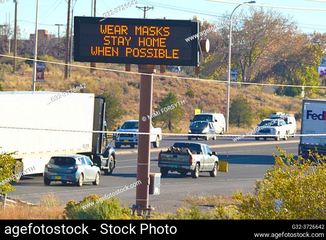 """Covid-19 sign by road, """"""""wear masks, stay home, when possible"""""""". New Mexico"""