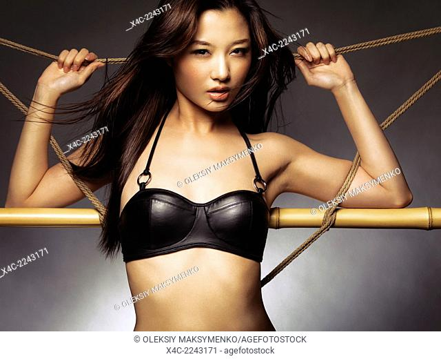 Beautiful sexy young asian woman with flying long hair wearing a black leather bra leaning against ropes and bamboo
