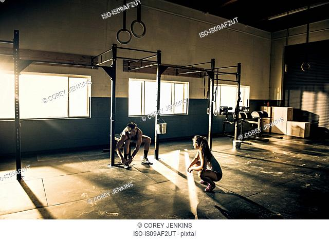 Female trainer talking to male client in gymnasium