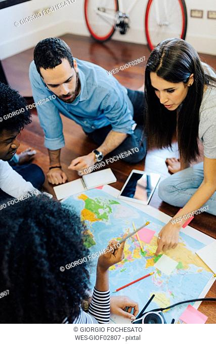 Group of friends looking at a world map