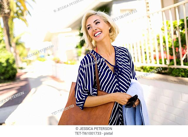 Woman wearing striped blouse walking street and smiling