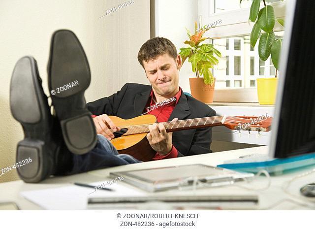 Mann im Anzug legt seine Füße auf den Schreibtisch und spielt konzentriert Gitarre