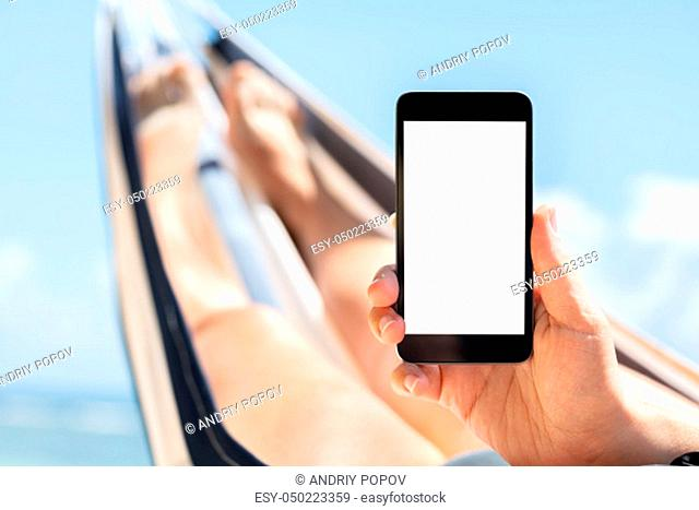 Young Woman Lying On Hammock Using Mobile Phone With White Screen Display Against Blue Sky