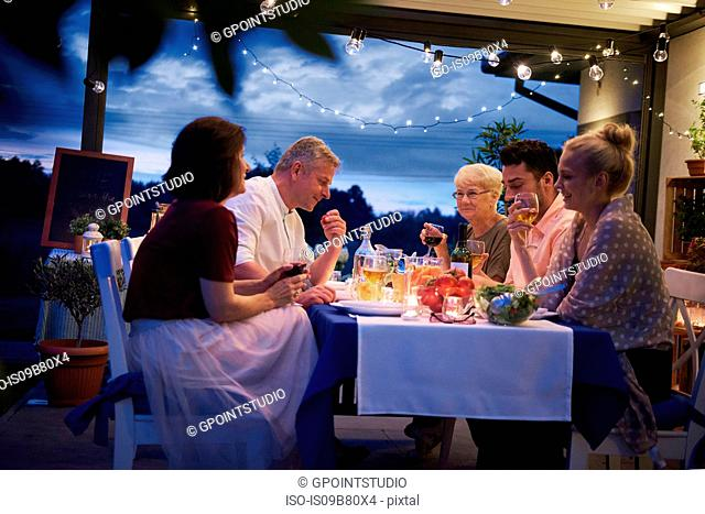 Group of people outdoors, sitting at table, enjoying meal