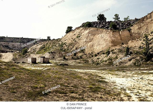 Abandoned quarry with dirt track and concrete blocks