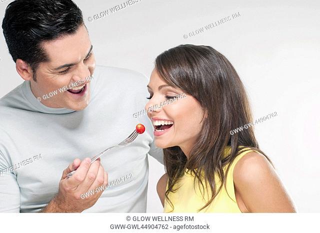 Man feeding woman a cherry tomato