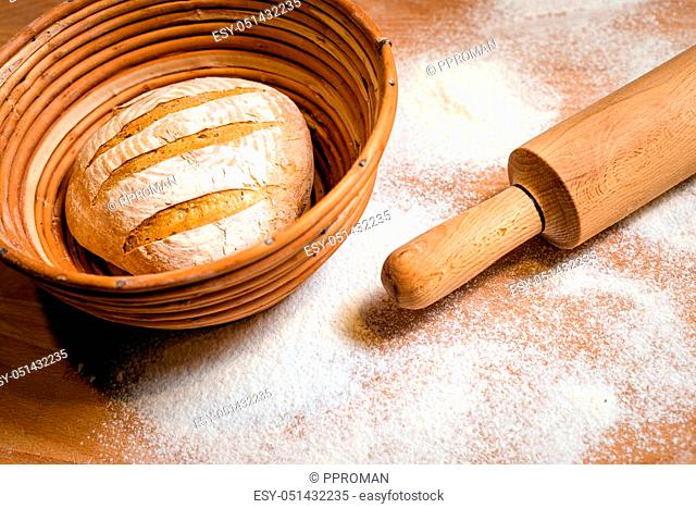 baker concept. Round bread on the wooden table with flour around