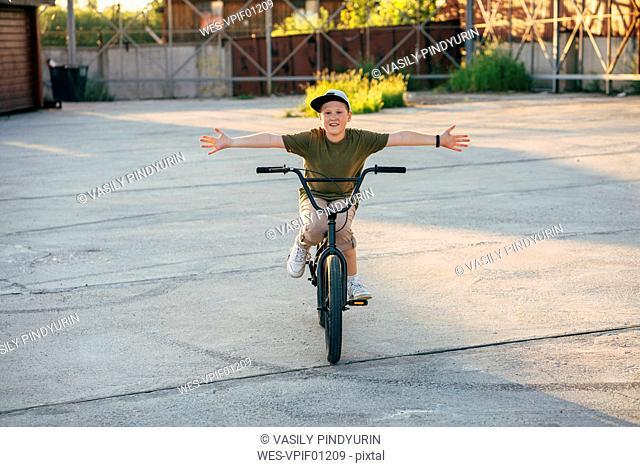 Portrait of smiling boy riding bmx bike freehanded