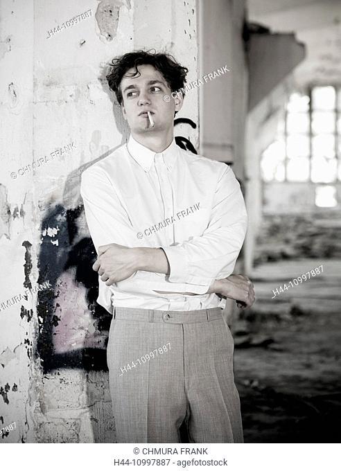 Young Man in White Shirt at Abandon Building Smoking