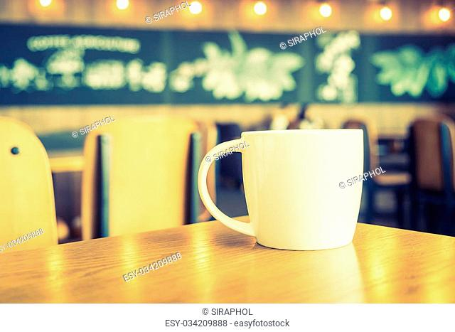 White coffee cup in coffee shop cafe - vintage filter