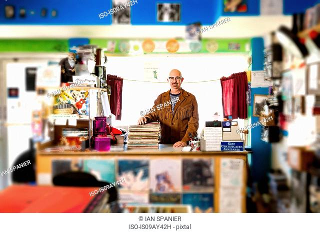 Portrait of mature man in record shop, leaning on stack of records
