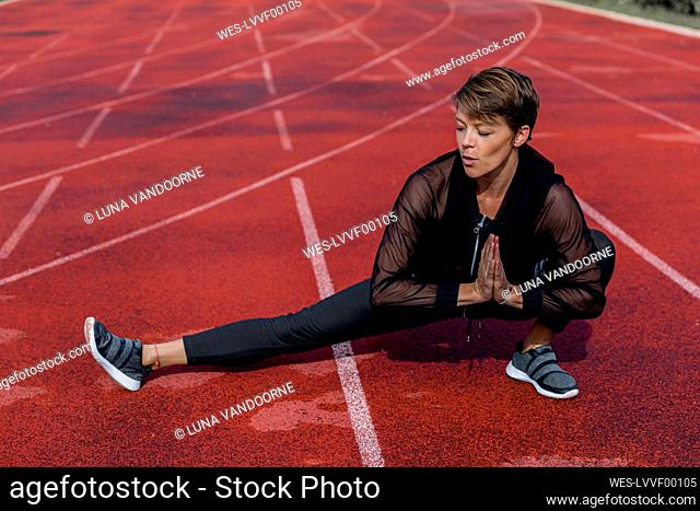 Sportive woman stretching on tartan track