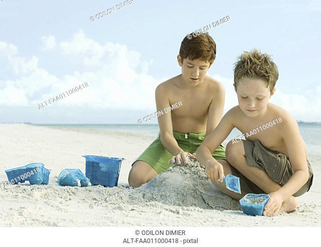 Boys building sand castle on beach