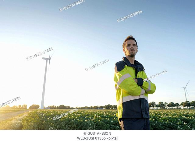 Engineer standing in a field at a wind turbine