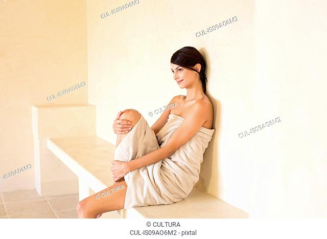 Young woman wrapped in a towel in sauna at spa
