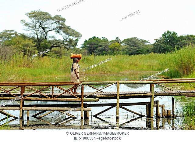 Woman with a load on her head on a bridge in Camp Kwando, lodge and campground on the Kwando River, Caprivi Strip or Okavango Strip, Namibia, Africa