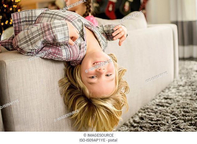 Portrait of boy lying upside down over sofa at christmas