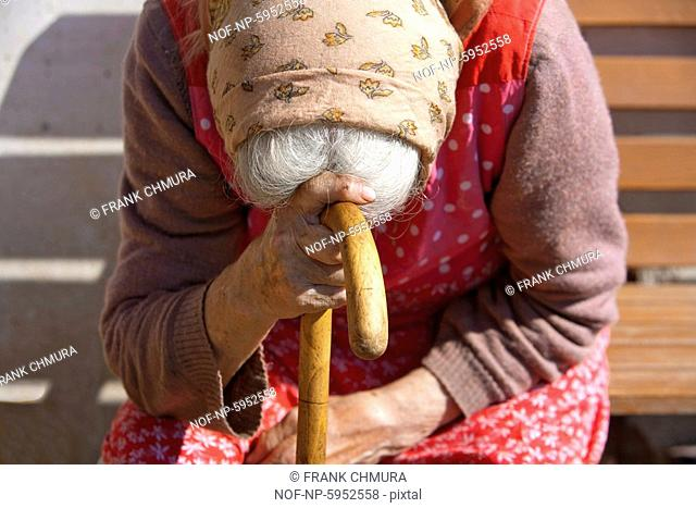 old peasant woman sitting leaning on a walking stick