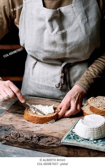 Woman spreading ricotta cheese onto slice of bread, mid section