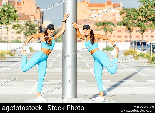 Portrait of smiling young active twins stretching while leaning on pole at parking lot during sunny day