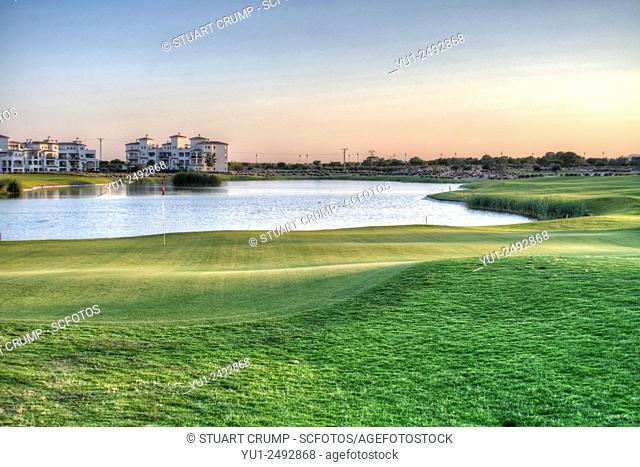 9th Green, fairway and water hazard with apartment in the distance at Hacienda Riquelme Golf Resort