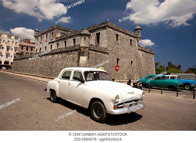Old American cars used as taxi in front of the castle-fortress used as a police station in Havana Vieja-Old Havana, La Habana, Cuba, West Indies