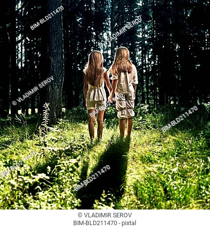 Caucasian girls holding hands in forest