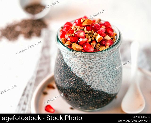 Healthy breakfast concept and idea - two colors chia pudding with organic raw pomegranate, almond and hemp grains. Glass jar with black charcoal and white vegan...