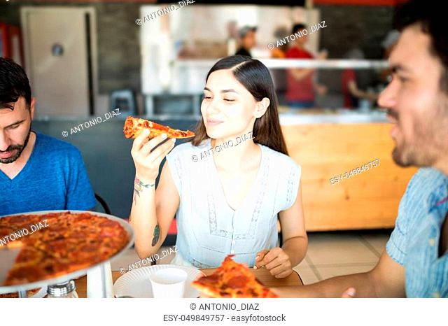 Pretty young woman holding pizza slice ready to eat while sharing pizza with male friends in pizza shop during day