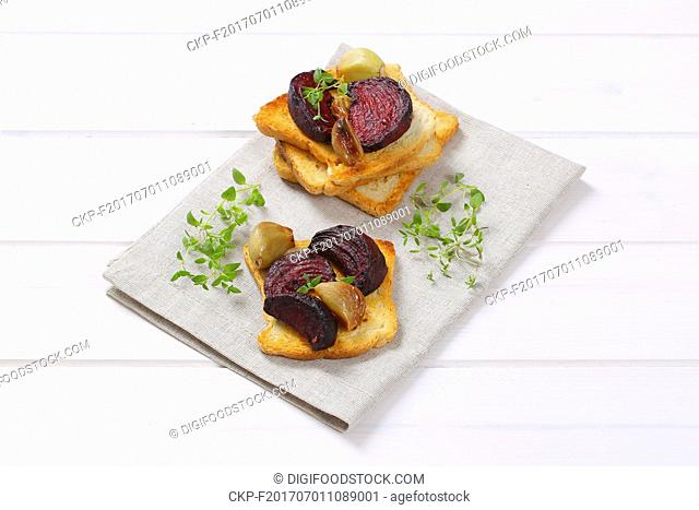 toast with baked beetroot, garlic and thyme on beige place mat