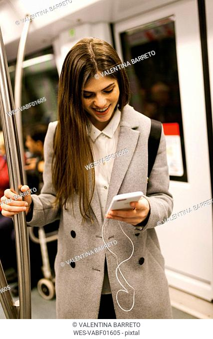 Young businesswoman using cell phone in underground train