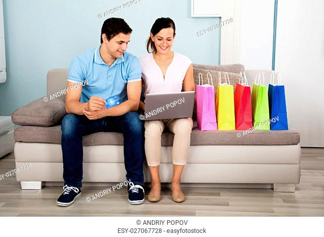 Young Happy Couple Shopping Online With Credit Card Sitting With Shopping Bags