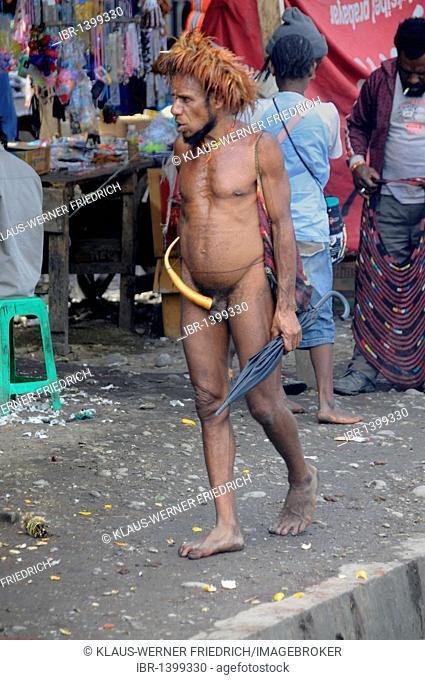 Dani man wandering the market place of Wamena, Baliem Valley, West Papua, former Irian Jaya, Indonesia, Southeast Asia