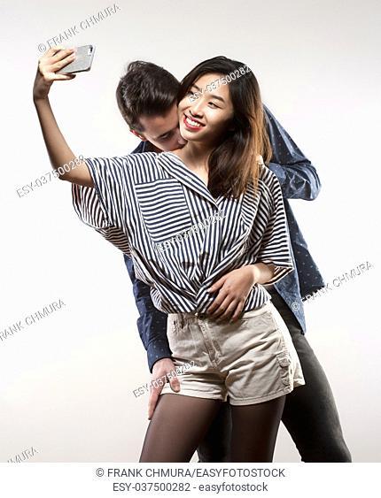 Teenage Girl Taking a Selfie While Being Kissed
