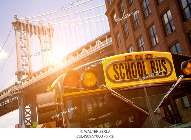 School bus below Manhattan Bridge, New York, USA