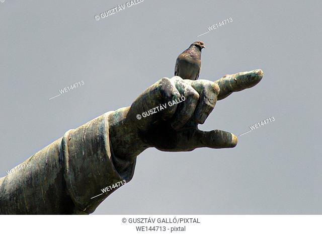 Ground breaking statue pigeon sitting on a back of the hand